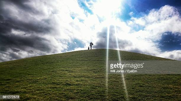Woman With Her Daughter Standing Top Of Hill Against Cloudy Sky