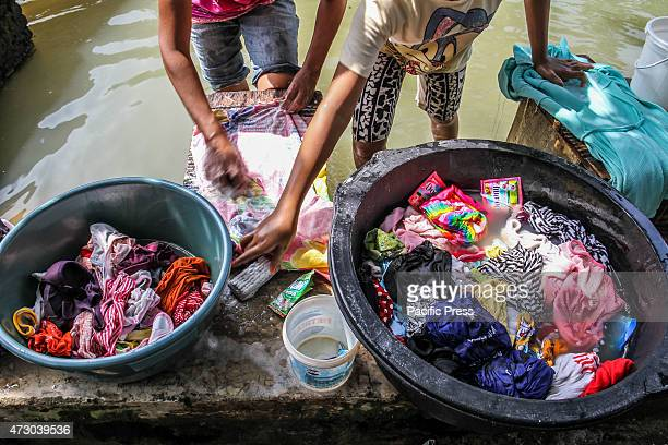 A woman with her daughter washing their clothes using polluted water from a canal in Tangerang Hundreds of toilets and drains empty into river and...