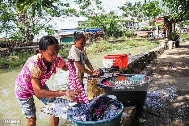 A woman with her daughter washing their clothes using the polluted water from a canal in Tangerang Hundreds of toilets and drains empty into river...