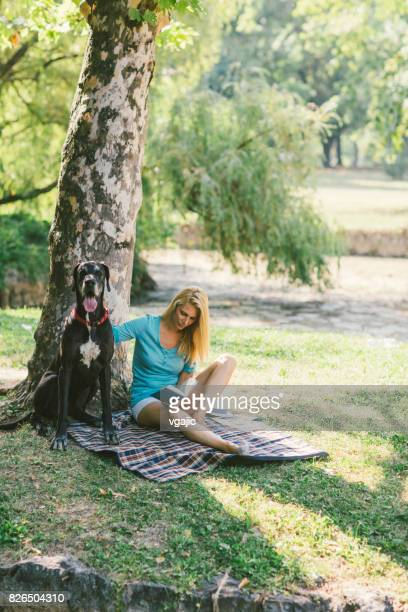 woman with her dog in park - only mid adult women stock pictures, royalty-free photos & images