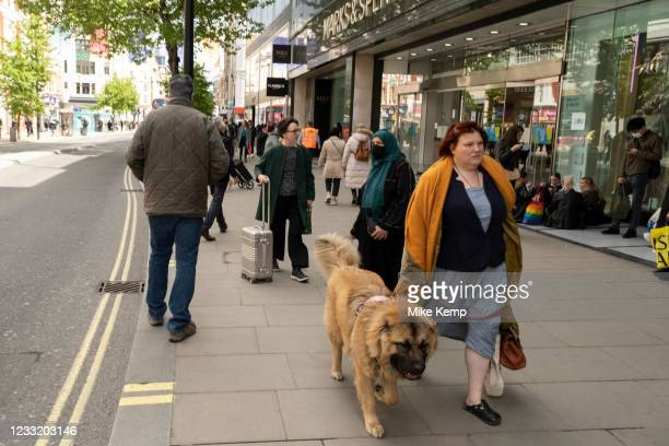 Woman with her dog out and about in the shopping district of Oxford Street, some wearing face masks and others not on 26th May 2021 in London, United...