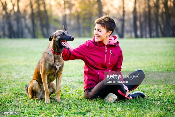 woman with her dog - belgian malinois stock photos and pictures