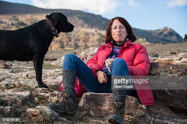 Woman with her dog resting on a rock
