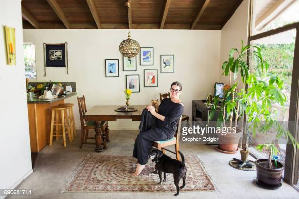 woman with her dogs at home - sala da pranzo foto e immagini stock