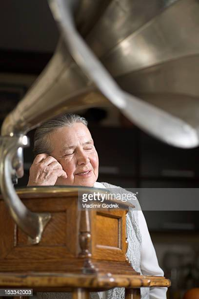 A woman with her eyes closed listening to a gramophone