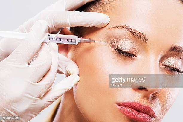 woman with her eyes closed receiving botox injection. - botox stock pictures, royalty-free photos & images