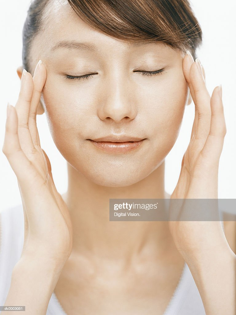 Woman With Her Eyes Closed Touching Her Face : Stock Photo