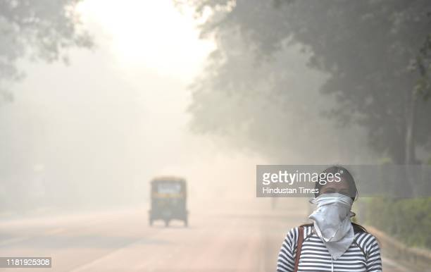 Woman with her face covered due to smog on Bhagwan Dass road near Mandi House during the morning on November 12, 2019 in New Delhi, India.