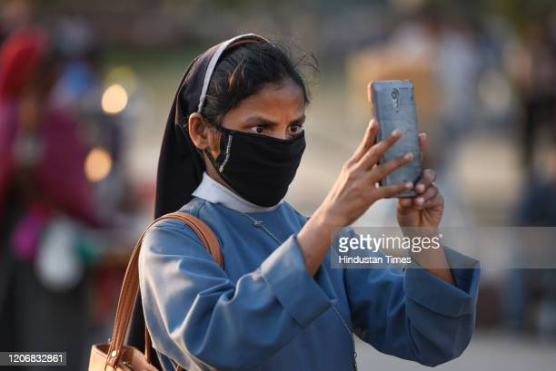 A woman with her face covered with a protective mask uses a mobile phone to capture a photo at India Gate monument as India suspended all tourist...