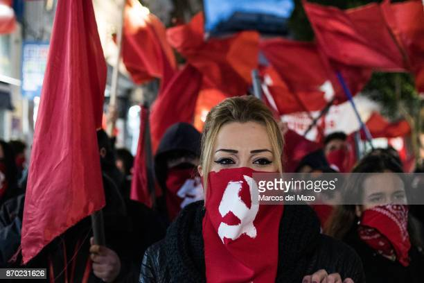 Woman with her face covered with soviet hammer and sickle during a demonstration for the 100th anniversary of the October Revolution.