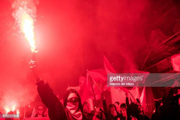 A woman with her face covered with soviet hammer and sickle raises a flare during a demonstration for the 100th anniversary of the October Revolution