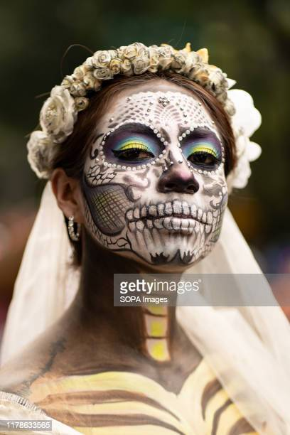 A woman with her face painted poses for a photograph during the Catrina Festival Thousands of people took to the streets of Mexico City to watch the...