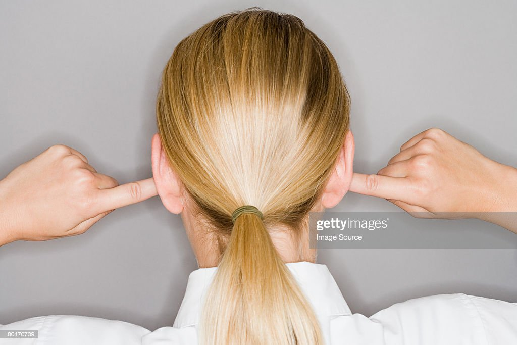 A woman with her fingers in her ear : Stock Photo