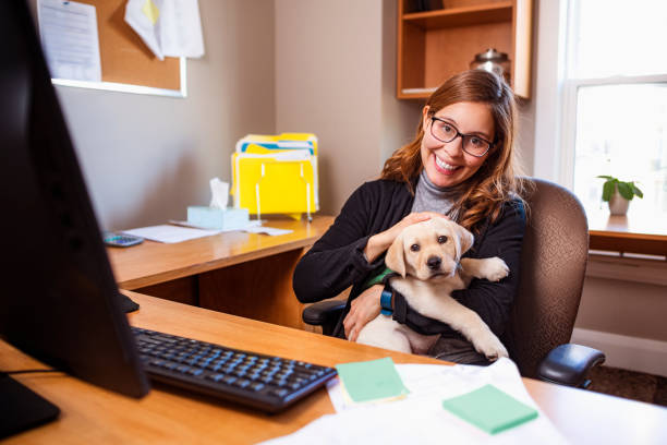 Woman with her foster guide dog puppy at her work