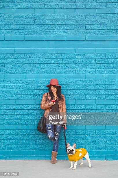 Woman with her French bulldog in front of blue wall