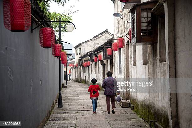 A woman with her granddaughter walks in the narrow alley decorated with red lanterns Shaoxing a city of more than 2000 years old is a famous travel...