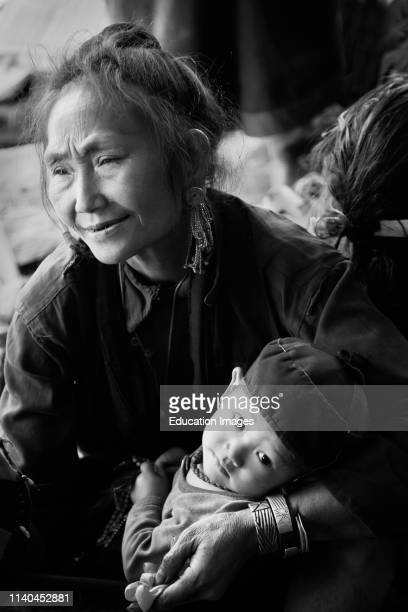 TRIBAL woman with her GRANDSON in traditional dress in her village near KENGTUNG also known as KYAINGTONG MYANMAR