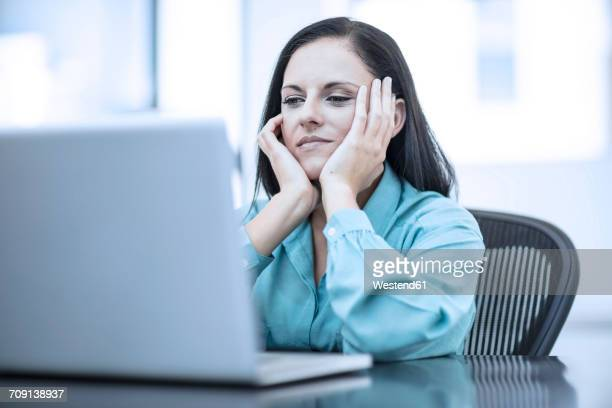 Woman with her head in her hands sitting in a office behind computer