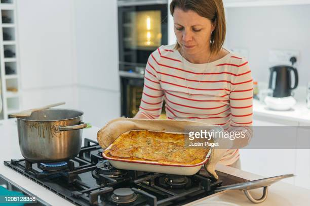 woman with her homemade lasagne - ready to eat! - lasagna stock pictures, royalty-free photos & images