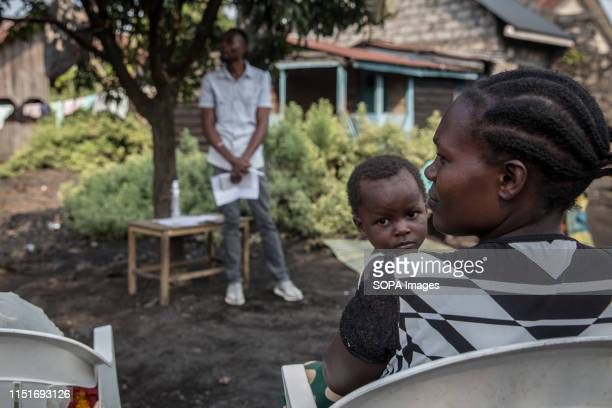 A woman with her kid attend a community meeting aimed at educating locals about the symptoms and treatment of Ebola as part of a community outreach...