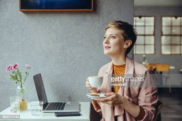 woman with her laptop enjoying a cup of coffee in a cafe - mid adult women stock pictures, royalty-free photos & images