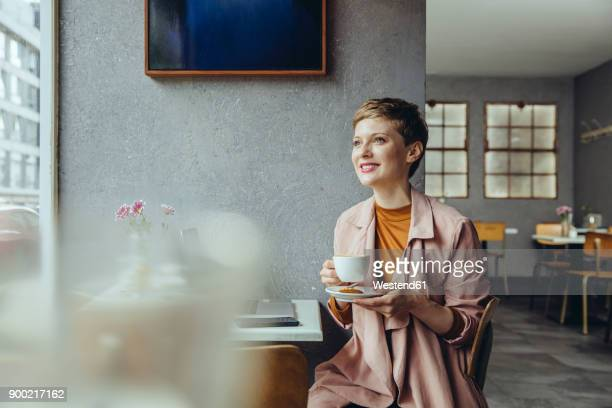 woman with her laptop enjoying a cup of coffee in a cafe - cafe imagens e fotografias de stock