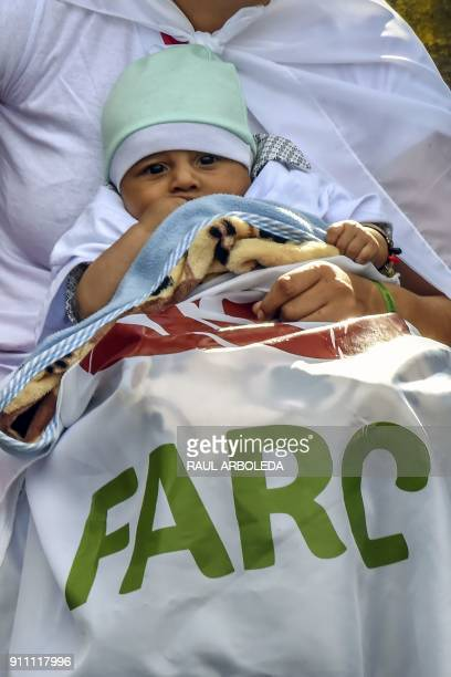 A woman with her little baby holds a banner with the logo of the FARC political party during the launch of the political campaign for president of...