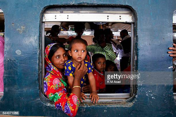 A woman with her little children looks through a window when she is on an over loaded train to go their village Millions of city dwellers travel to...