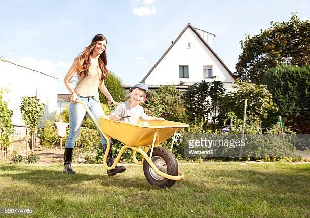 woman with her little son sitting in a wheelbarrow - wheelbarrow stock photos and pictures