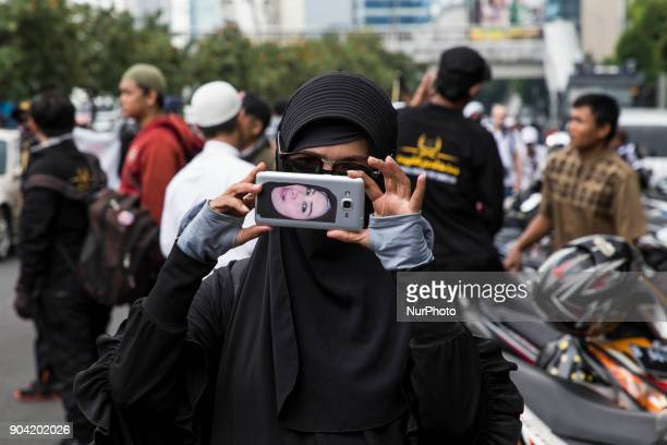 A woman with her profile picture at the back of the smartphone took picture of the demonstration banner Hundreds of muslims from Indonesian Islam...