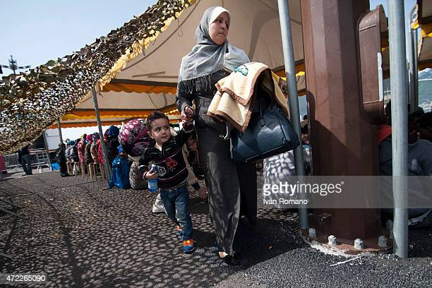 A woman with her son walk after disembarking from military ship 'Bettica' following a rescue operation at sea on May 5 2015 in the port of Salerno...