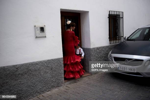 A woman with her son wearing a typical Flamenco dress seen in a street of Albaicin neighbourhood during the Dia de las Cruces in GranadaEl día de la...