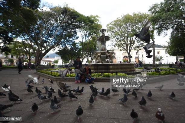 A woman with her sons play in a park of Antigua ahead of the XXVI IberoAmerican Summit in Guatemala on November 142018 Fourteen heads of state will...