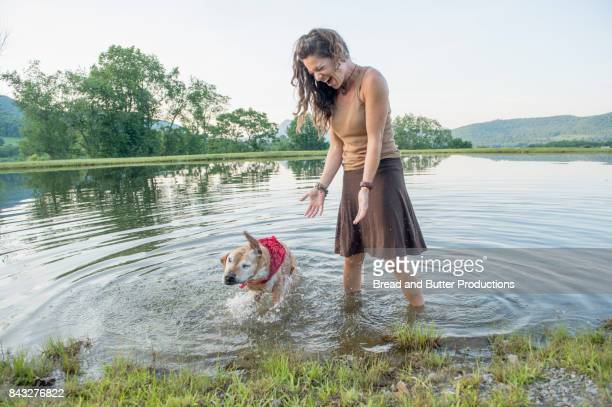 woman with her staffordshire bull terrier dog in pond outdoors - american staffordshire terrier stockfoto's en -beelden