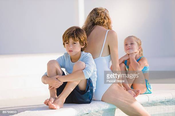 Woman with her two children sitting at the poolside
