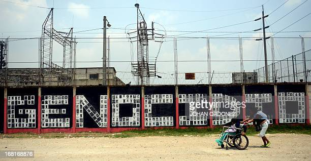 A woman with her two children walks by a wall with the word 'Genocide' made with portraits of missing persons during the internal armed conflict in...