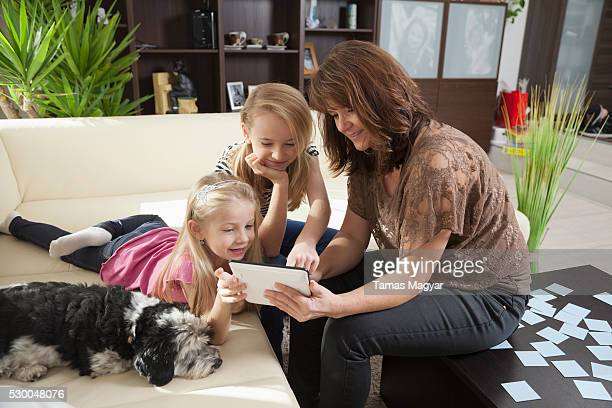 woman with her two daughters playing games on a digital tablet in a living room, bavaria, germany - little girls socks stock photos and pictures