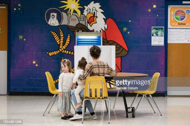 A woman with her two young daughters marks down her vote on a ballot for the Democratic presidential primary election at a polling place in Armstrong...