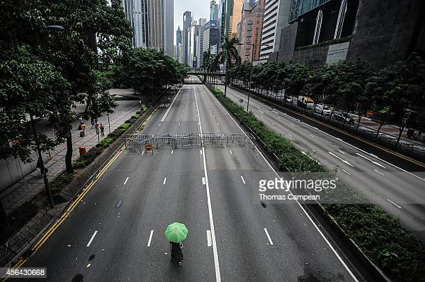 A woman with her umbrella walks on an empty street occupied by prodemocracy demonstrators on October 1 2014 in Hong Kong Thousands of pro democracy...