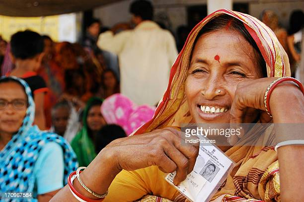 A woman with her voter identity card awaiting her turn West Bengal India