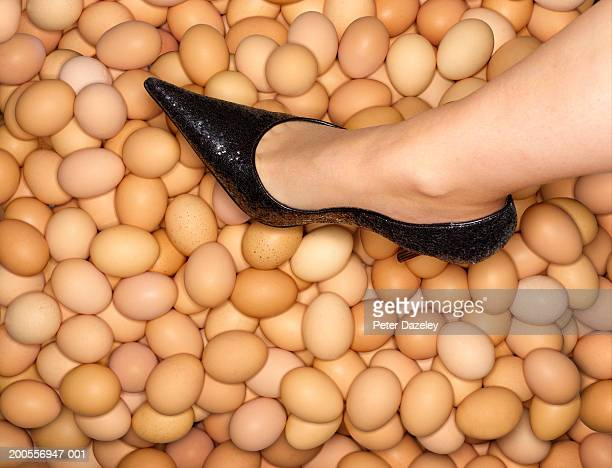 woman with high heeled shoes walking on egg shells, low section - partie inférieure photos et images de collection