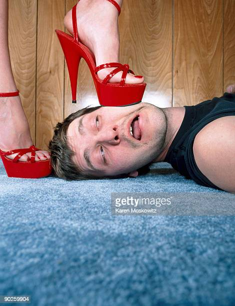 woman with high heels stepping on man - feet torture stock pictures, royalty-free photos & images