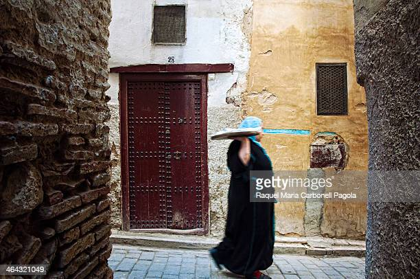 Woman with hijab and djellaba bringing bread to an oven in the Medina