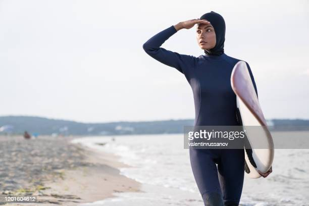 woman with hijab carrying surfboard in sea - swimwear stock pictures, royalty-free photos & images