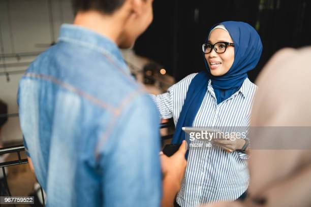 Woman with hijab in leadership role.
