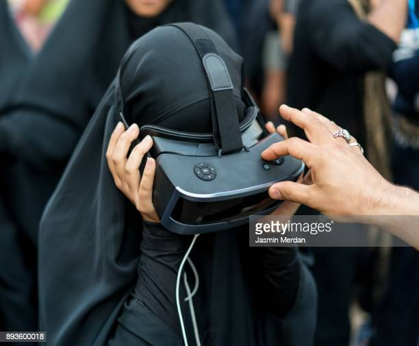 Woman with hijab using VR on street