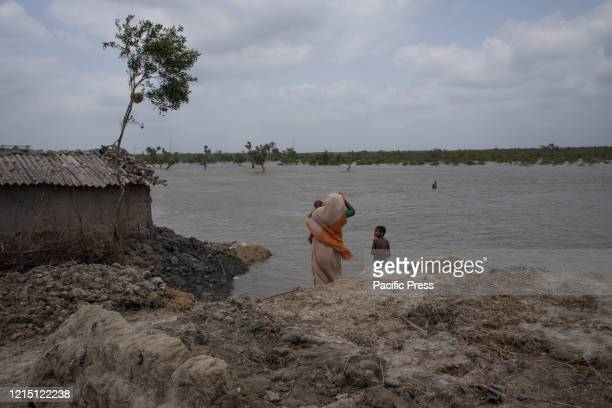 A woman with his 2 children standing beside their flooded land waiting for her other child who has gone to get food for his family They have lost...