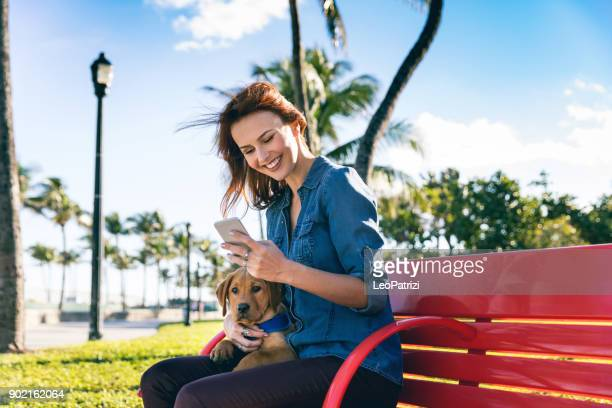 Woman with his Labrador puppy during a beautiful day at the park in Miami Beach.
