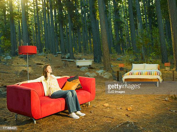 a woman with home furnishings sitting outdoors in the woods - out of context stock pictures, royalty-free photos & images