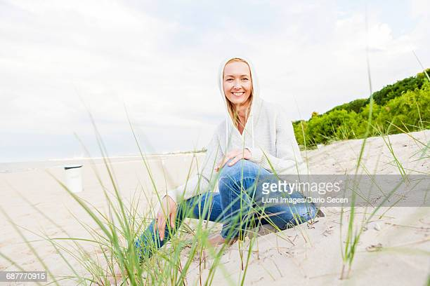 Woman with hooded shirt sitting on sandy beach